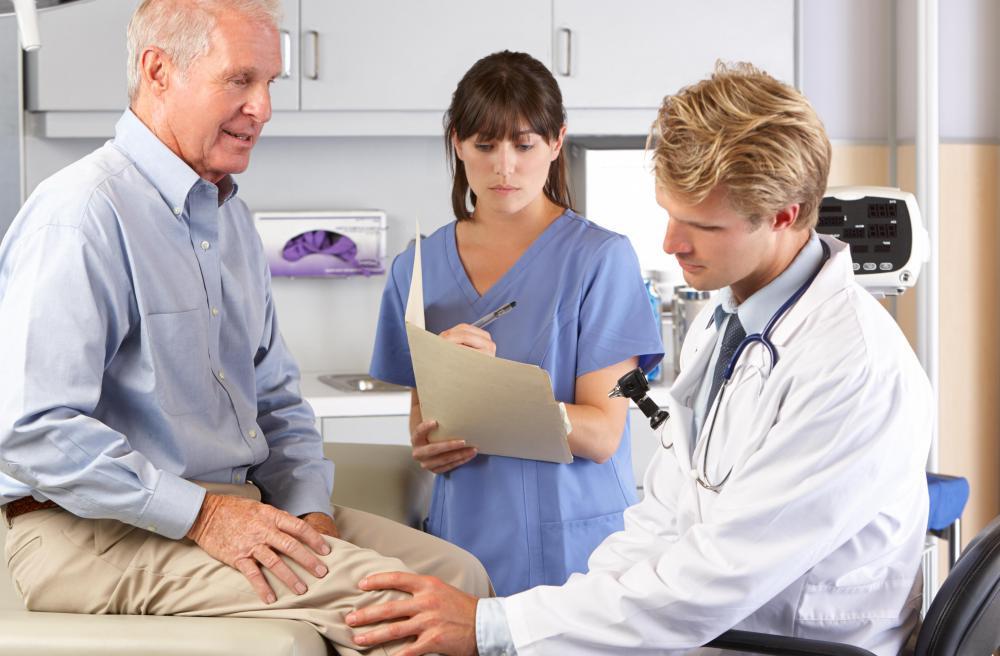 Доктор осматривает колено пожилого мужчины